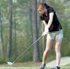 girl on golf course hitting golf ball